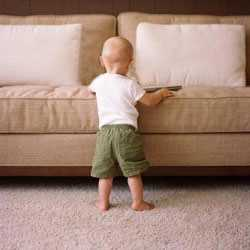 Toddler standing against a sofa on carpet after carpet and upholstery cleaning